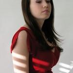 Steph poses in her crimson top in a studio